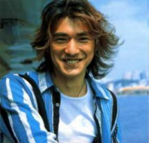 Takeshi Kaneshiro with high ligted hairstyle with full of layers and long side bangs with beautiful background