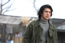 Takeshi Kaneshiro in K20 with cuts to the face in green jacket.jpg