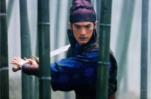 Takeshi Kaneshiro in movie House of Flying Dragon with sword in surounding of bambos